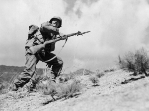 Taking the hill. Pfc. John J. Allen of Company E in the 25th Infantry Division leads his men in attack on the west central front in Korea, March 30, 1951.